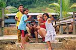 Un groupe d'enfants Iban Dayak avec une caméra à l'extérieur de leur longère sur fleuve Rajang près Kapit à Sarawak, à Bornéo, en Malaisie, du Nord-Ouest l'Asie du sud-est, Asie et touristique