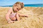 Petite fille jouant avec le sable sur la plage, Cabo San Lucas, Mexique