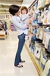 Femme portant son fils et faire du shopping dans un supermarché