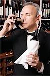 Businessman smelling cork of a wine bottle