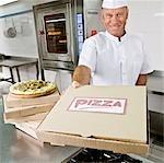 Chef tenant une boîte à pizza