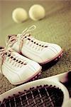 Gros plan d'une paire de chaussures avec une raquette de tennis et balles de tennis