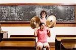Zwei Studenten Spaß mit Becken in einem Klassenzimmer