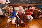 Drei Studenten spielen Musikinstrumente in einem Klassenzimmer
