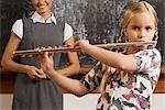 Schulmädchen spielt eine Flöte in einem Klassenzimmer