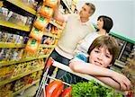 Portrait d'un garçon dans un supermarché avec ses parents shopping derrière lui