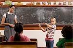 Schulmädchen spielt eine Flöte mit ihrem Lehrer und Klassenkameraden in einem Klassenzimmer