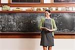 Female teacher smiling in in front of a blackboard