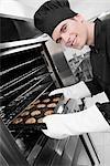 Chef prenant sur un plateau de biscuits du four