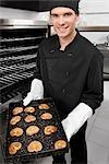 Chef tenant un plateau de biscuits