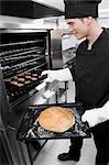 Chef en prenant un petit pain et biscuits du four