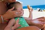 Woman applying suntan lotion to her daughter,Cabo San Lucas,Mexico