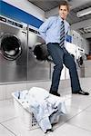 Businessman putting a briefcase into a washing machine