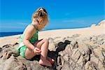 Petite fille assise sur un rocher, Cabo San Lucas, Mexique