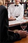 Femme tenant un verre de vin dans un bar