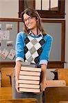 Female teacher holding books in a classroom