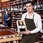 Sales clerk showing a crate of wine bottles