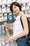 Woman choosing baby bottle in a supermarket
