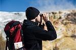 Man looking through binoculars,Mammoth Hot Springs,Yellowstone National Park,Wyoming,USA