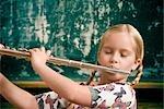 Schulmädchen spielt eine Flöte vor einer Tafel