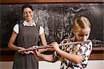 Schulmädchen spielt eine Flöte mit ihrem Lehrer lächelnd vor einer Tafel