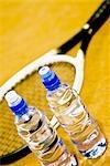 Gros plan de deux bouteilles d'eau et une raquette de tennis