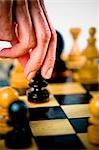 Gros plan de la main d'une personne tenant une pièce d'échecs