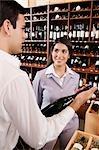 Sales clerk holding a wine bottle beside a businesswoman smiling