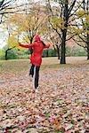 Woman Skipping through Autumn Leaves