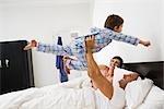 Famille jouant dans son lit