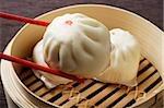 red chopstick holding dim sum (bao)
