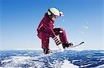Girl in jumpsuit grabbing board mid-air.