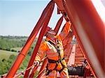 Crane Worker Inspecting Arm Of Crane