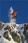 Skier jumping off rocks.