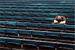 Ein Mann sitzt in einem Hörsaal mit seinem Kopf in seinen Armen ruhen