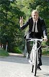 Businessman biking through the forest