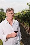 Porträt des Mannes im Weinberg mit einem Glas Wein