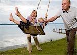 grands-parents avec petit-fils sur swing