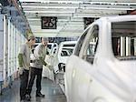 Travailleurs d'usine de voiture discutant des voitures