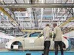 Travailleurs d'usine inspecter la coque de la voiture