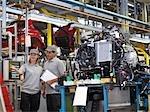 Travailleurs d'usine de voiture avec des pièces de voiture