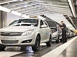 Travailleur vérifiant les voitures sur la ligne de Production