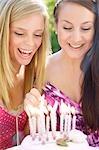 Gros plan de deux adolescentes, allumant des bougies sur un gâteau d'anniversaire