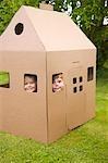 Jungen und Mädchen mit Blick aus den Fenstern einen Karton Spielhaus