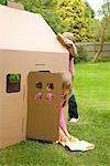 Junge und Mädchen spielen und Reinigen der Außenflächen des einen Karton Spielhaus