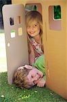 Nahaufnahme von einer jungen und Mädchen lächelnd in der Tür von einem Karton Spielhaus