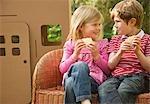 Jungen und Mädchen essen Kekse einander betrachten