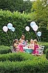 Groupe de jeunes filles ayant une partie dans un jardin, sourire et rire