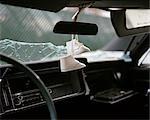 1960ER 1970ER JAHREN PAAR WEIßE BABYSCHUHE HÄNGEN VON RÜCKSPIEGEL ZERSTÖRTEN AUTOS MIT ZERBROCHENEN GLAS WINDSCHUTZSCHEIBE