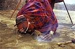 AMBOSELI NATIONAL RESERVE KENYA AFRICA MASAI MAN STARTING FIRE